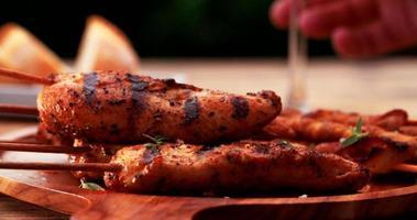 Grillmahlzeit auf einem Holztisch im Freien mit Hühnchen-Spießen