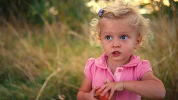 una bambina carina in un campo con in mano una mela video
