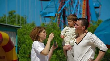 jovem família em parque de diversões