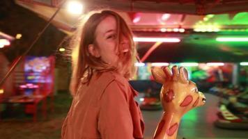 mulher bonita se divertindo andando de carrossel em parque de diversões