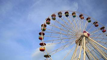 panning shot of Ferris Wheel at amusement park with blue sky