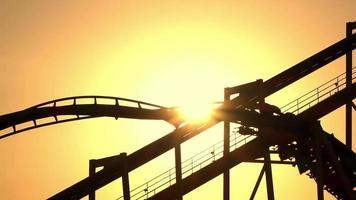 SLOW MOTION: Sunset sun shining through extreme roller coaster ride