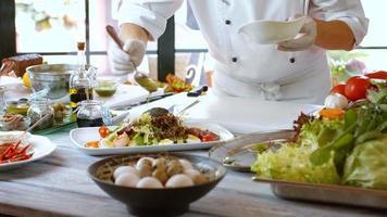 Löffel gießt Flüssigkeit auf Salat.
