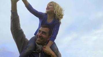 la bambina gioca a Superman sulle spalle di papà