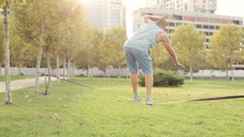 mec marche en slackline dans un parc public