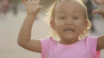 linda niña juega al mono y asusta en el parque público