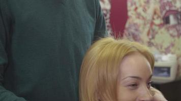 peluquero profesional mira el resultado del trabajo. Feliz chica rubia con peinado de volumen en salón de belleza