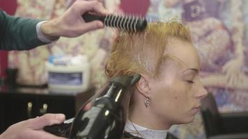 Professional barber dry wet hair of blonde girl using hairdryer and comb in beauty saloon. Hair care video