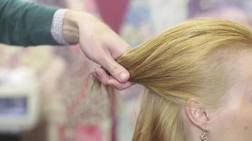 Professional barber divide hair of blonde girl on parts, fixing by bobby pin in beauty saloon video