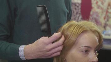 Peluquero profesional peine el cabello a la chica rubia con un peine recto en un salón de belleza. peinado de volumen