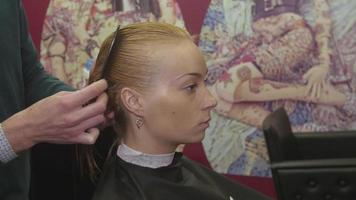 Professional barber comb wet hair of blonde girl in beauty saloon. Hair care. Prepare to haircut video
