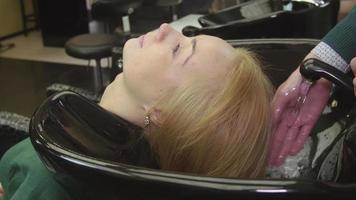 Peluquero profesional sintonizar agua para lavar el cabello de la joven rubia en salón de belleza. cuidado del cabello