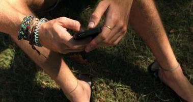 homem sentado na grama usando telefone celular video