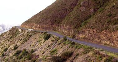 Foto de drone de alto ângulo de ciclista andando pela estrada na montanha video