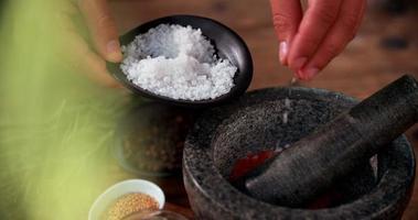 Salz in einen Mörser und Stößel bei der Herstellung von Fleischgewürzen hinzugefügt