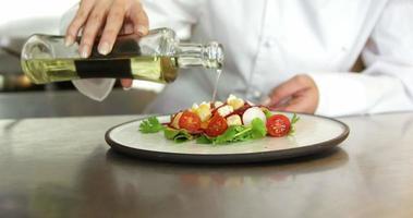 Chef vertiendo aderezo para ensaladas sobre una ensalada video