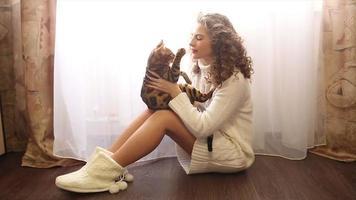 garota brincando com o gato de Bengala no chão. video