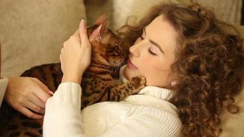 garota acariciando e beijando seu gato de bengala. video
