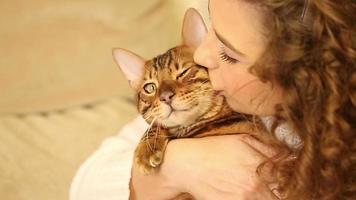 a garota abraça e beija um gato de bengala. fechar-se.