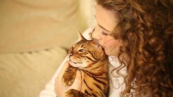 garota abraçando e brincando com o gato de bengala. rir. video