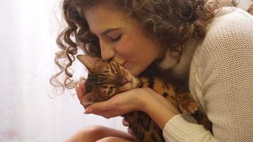 menina beijando um gato de bengala. video