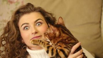 o gato de bengala e a garota se divertindo se mordem. video