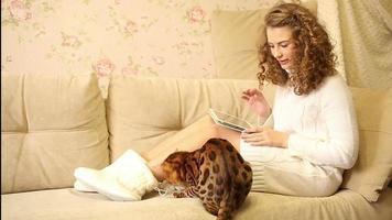 garota jogando em um computador tablet. gato de bengala. animal. video