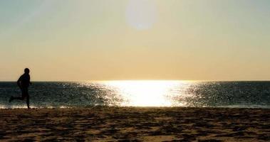 coureur masculin en cours d'exécution sur la plage, silhouette coucher de soleil, mouvement lent