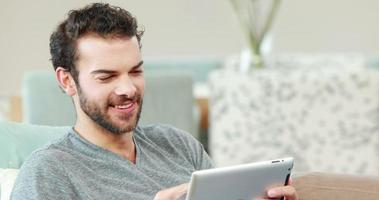 felice giovane uomo utilizzando il suo tablet video