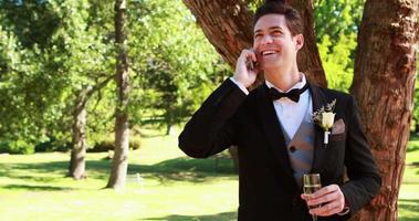 Happy groom drinking champagne and chatting on phone