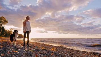 Young woman with a dog standing next to the shore of a lake or the sea. At sunset, looking into the distance, dreaming