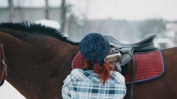 Frau setzte einen Sattel auf ein Pferd