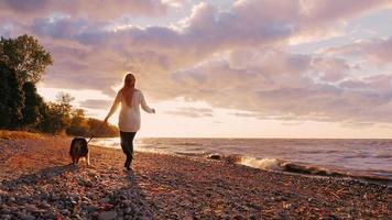 junge Frau, die mit einem Hund am Ufer des Sees Ontario bei Sonnenuntergang geht