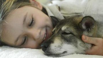 niña divirtiéndose perro susurrando en su oído