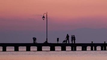 famiglia che cammina con il cane su un molo al tramonto