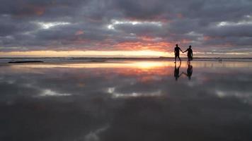 camminare sulla spiaggia con un riflesso perfetto nella sabbia. hd