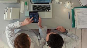 Top view of Doctors discussing images of x-ray scan on tablet