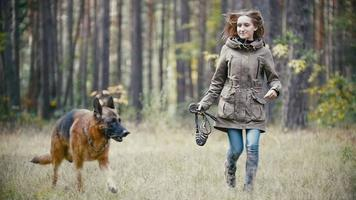 Young woman holding a leash running with a shepherd dog in autumn forest, slow motion video