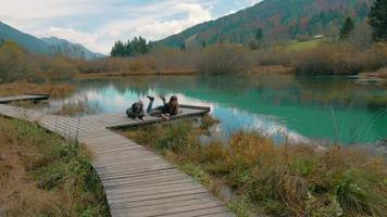 cámara lenta una niña junto a un lago con su perro