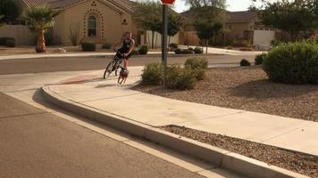 Il ciclista è trainato da un cane sul tipico marciapiede del quartiere dell'Arizona