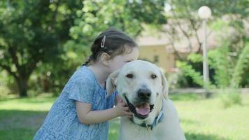 une petite fille jouant avec son gros chien blanc