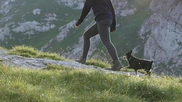 close-up: jovem feliz com seu pequeno cachorro de estimação em uma incrível aventura de caminhada