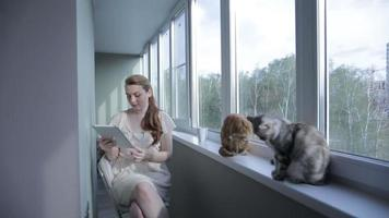 chica con tableta sentada junto a la ventana y bebida de la taza.