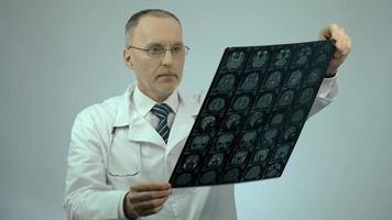 neurochirurgo che controlla l'immagine del cervello di risonanza magnetica, guardando la fotocamera, servizi di assistenza sanitaria