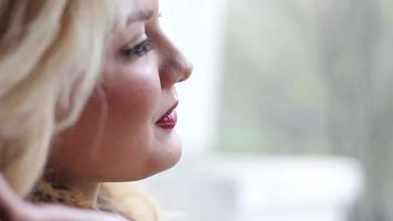 Porträt der schönen jungen Frauen in der Nähe des Fensters lächelnd und korrigiert Frisur