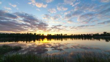 nuvens sobre um pântano com plantas e uma árvore. lapso de tempo um pôr do sol com nuvens brilhantes sobre um reservatório. vídeo sobre o rio. reflexo de nuvens.