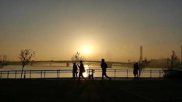 câmera lenta de pessoas anônimas no calçadão ao pôr do sol após uma tempestade.