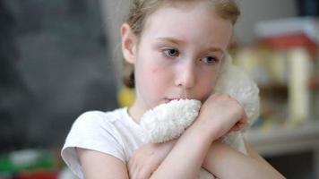 trauriges kleines Mädchen mit Teddybär im Kinderzimmer.