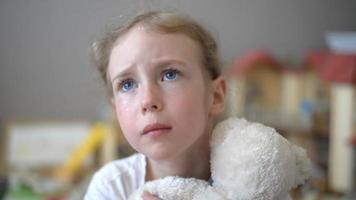 weinendes kleines Mädchen mit Bär im Kinderzimmer.