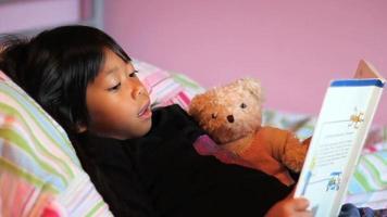 niña asiática lee un libro de cuentos al oso de peluche